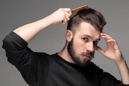 peineta: joven peinar su cabello sobre fondo gris Foto de archivo