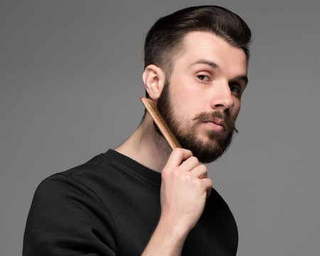 comb hair: young man comb his beard and moustache on gray background Stock Photo