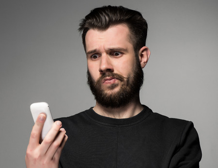 beau jeune homme: Portrait d'un homme perplexe parler au téléphone sur un fond gris Banque d'images