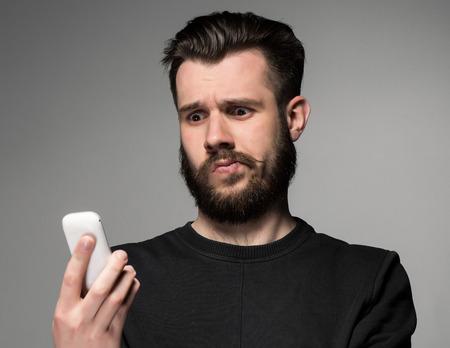 Portret van verbaasd man praten over de telefoon op een grijze achtergrond Stockfoto