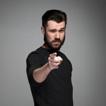 ひげと口ひげを生やして、若い男は、灰色の背景にカメラに向かって指している指します。