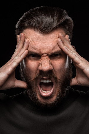 rage: Portrait of young frightened  crying man with a beard and mustache in studio on black background. concept of rage Stock Photo
