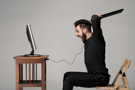 laptop hands: Angry man is destroying a keyboard and monitor of computer on gray background Stock Photo