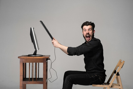 Angry man is destroying a keyboard and monitor of computer on gray background Standard-Bild