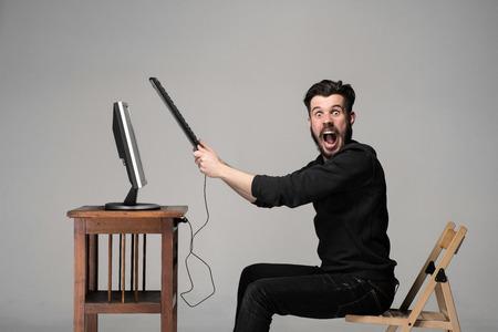 gente loca: Hombre enojado está destruyendo un teclado y un monitor de ordenador en el fondo gris Foto de archivo