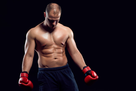 dauntless: Muscular man - young caucasian boxer in red gloves standing over black background Stock Photo