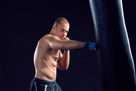 punched out: Young boxer boxing over  the black background