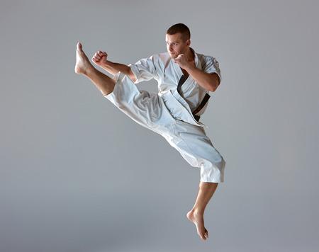 patada: El hombre en el kimono blanco y cinturón negro de karate de formación sobre fondo gris.