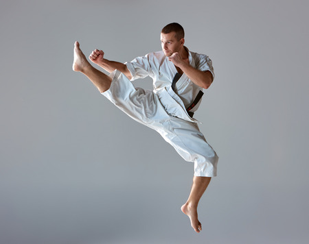 arts: Man in white kimono and black belt training karate over gray background.