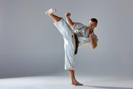 Man in witte kimono en zwarte band karate training over grijze achtergrond.