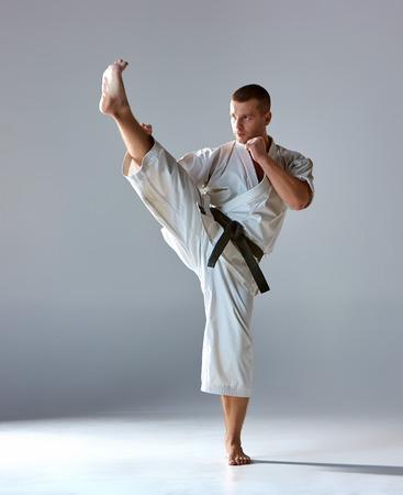 Man in white kimono and black belt training karate over gray background.
