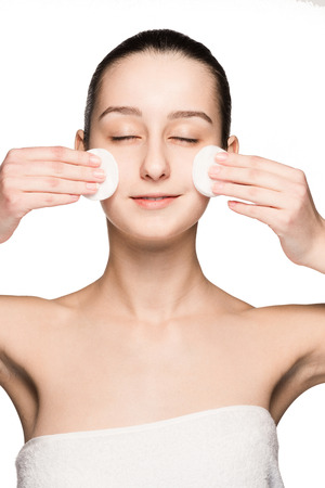 skin care woman removing face with cotton swabs - skin care concept. Facial closeup of beautiful Caucasian model with perfect skin. Girl isolated on white background Stock Photo - 41233906