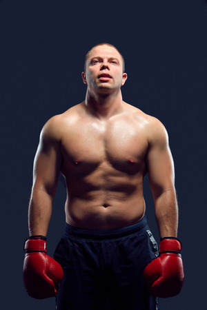 intrepid: Muscular man - young caucasian boxer in red gloves standing over black background. arms down down and along the body Stock Photo
