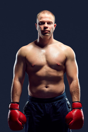 dauntless: Muscular man - young caucasian boxer in red gloves standing over black background. arms down down and along the body Stock Photo