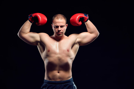 brawny: Muscular man - young caucasian boxer in red gloves standing over black background. demonstration of strength and power