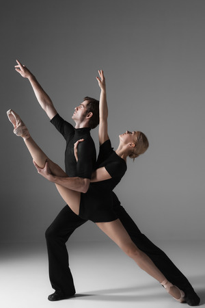 male and female: The two young modern ballet dancers in black suits posing over gray studio background