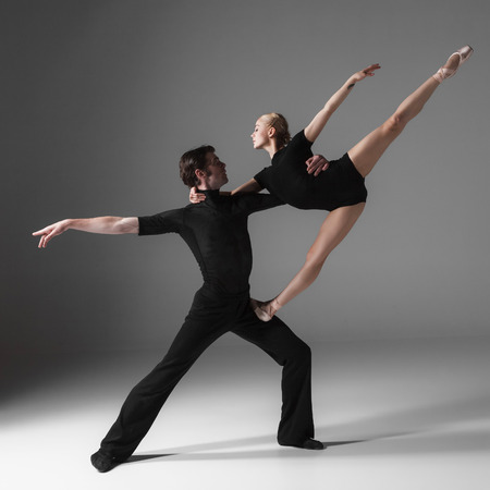 dancers: The two young modern ballet dancers in black suits posing over gray studio background