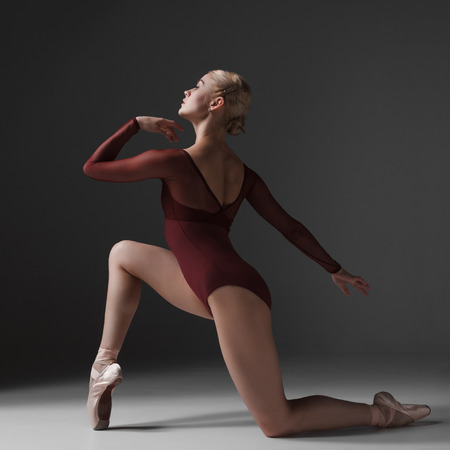 young beautiful modern style dancer posing on a studio gray background photo