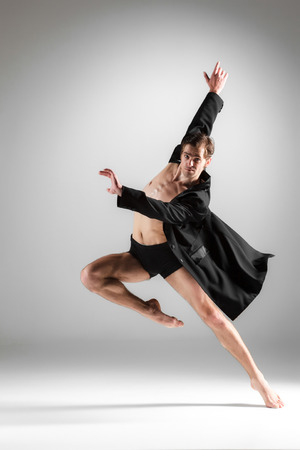 The young attractive modern ballet dancer in black jacket over white background.