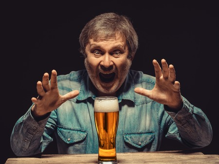Enjoying his favorite beer.  The front view of handsome screaming man as fan in denim shirt with glass of beer, sitting at the wooden table. Concept of enthusiasm and ecstasy