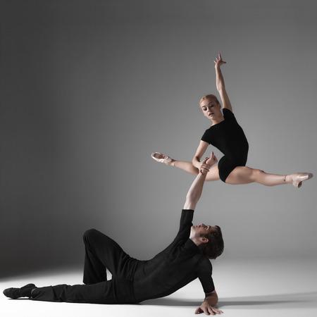 회색 스튜디오 배경 위에 검은 정장에 두 젊은 현대 발레 댄서