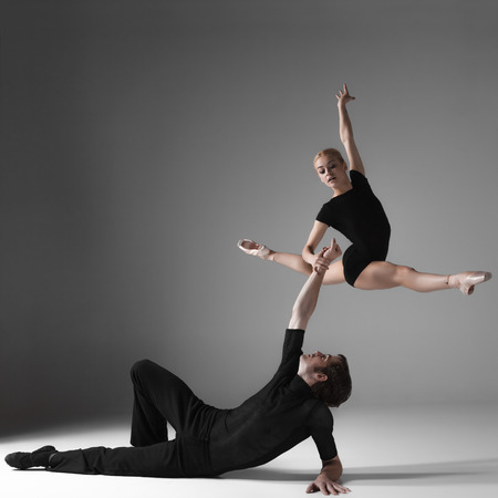 man jump: The two young modern ballet dancers in black suits over gray studio background