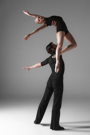 ballet: The two young modern ballet dancers in black suits posing over gray studio background