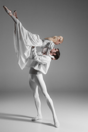 Two young classic ballet dancers practicing. attractive dancing performers  in white suits over gray background 스톡 콘텐츠