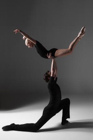 T�nzerIn: Die beiden jungen modernen Ballett-T�nzer in schwarzen Anz�gen posiert auf grauem Hintergrund Studio