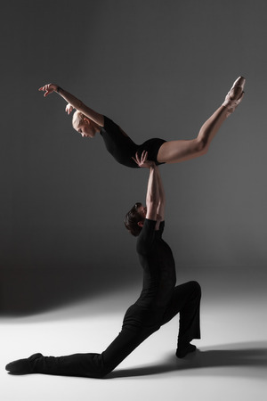 modern ballet dancer: The two young modern ballet dancers in black suits posing over gray studio background