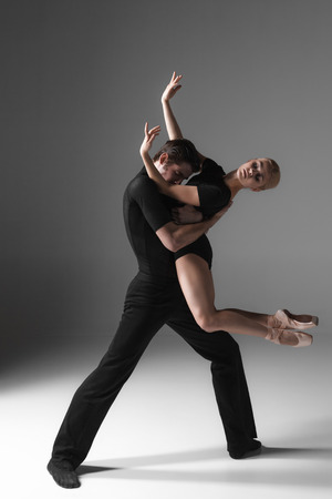 The two young modern ballet dancers in black suits posing over gray studio background