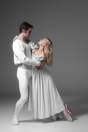 Two young classic ballet dancers practicing. attractive dancing performers  in white suits over gray background Фото со стока