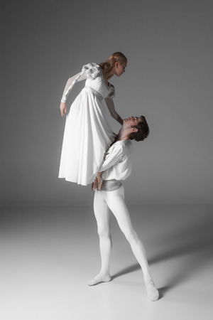 romeo and juliet: Two young classic ballet dancers practicing. attractive dancing performers  in white suits over gray background Stock Photo