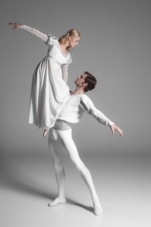 Dos jóvenes bailarines de ballet clásico que practican. ejecutantes baile atractivas en trajes blancos sobre fondo gris Foto de archivo