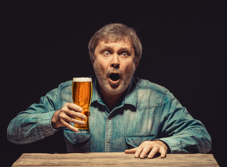 emotional love: The front view of handsome man as enchanted and emotional fan in denim shirt with glass of beer, sitting at the wooden table. Concept of  surprise and exciting spectacle