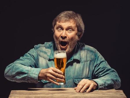 �xtasis: Disfrutando de su cerveza favorita. La vista frontal del hombre gritando apuesto como ventilador en camisa de mezclilla con un vaso de cerveza, sentado en la mesa de madera. Concepto de entusiasmo y el �xtasis Foto de archivo