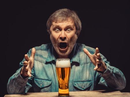 éxtasis: Disfrutando de su cerveza favorita. La vista frontal del hombre gritando apuesto como ventilador en camisa de mezclilla con un vaso de cerveza, sentado en la mesa de madera. Concepto de entusiasmo y el éxtasis Foto de archivo