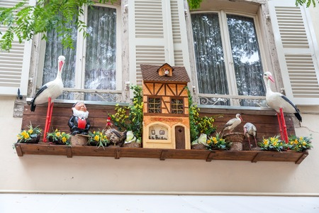 originally: The originally decorated window in Strasbourg, France. storks and flowers Stock Photo