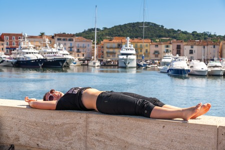 Girl and yachts on the coast of Saint Tropez, France. girl lying on the waterfront photo