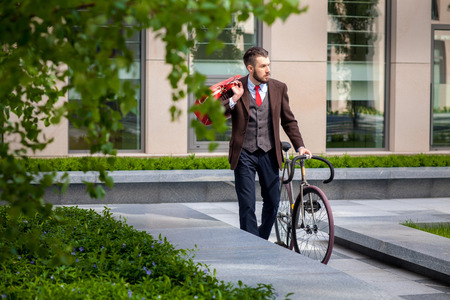 Handsome businessman in a jacket and red tie and his bicycle on city streets. The concept of the modern lifestyle of young men