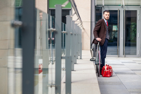 Handsome businessman in a jacket and red tie and his bicycle on city streets. red bag lies next. The concept of the modern lifestyle of young men Stock Photo