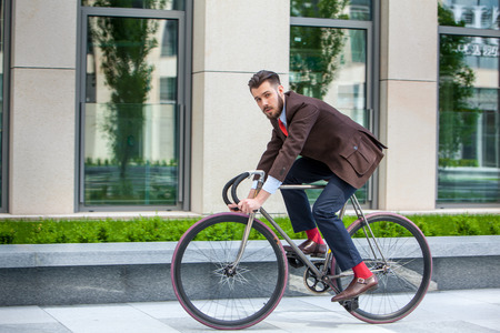 bicycle walk: Handsome businessman in a jacket riding on his bicycle on city streets. The concept of the modern lifestyle of young men Stock Photo