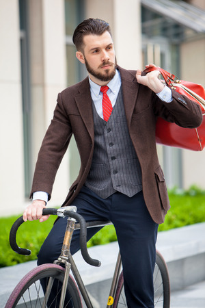 Handsome businessman in a jacket with red bag sitting on  his bicycle on city streets. The concept of the modern lifestyle of young men Stock Photo