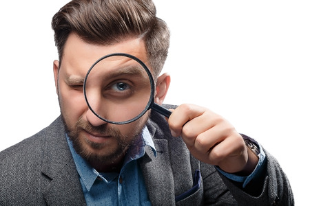 magnifying glass man: Man in a jacket with magnifying glass isolated on white background