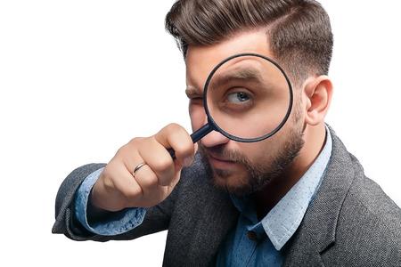 Man in een jasje met een vergrootglas op een witte achtergrond Stockfoto