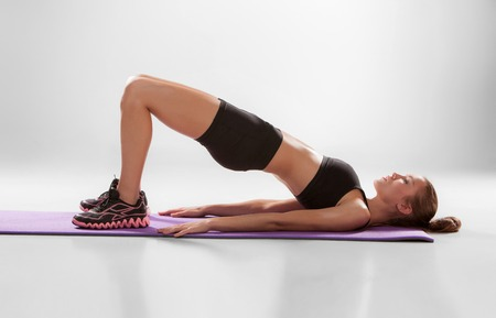 lying on stomach: Attractive woman do fitness exercise on a lilac mat on grey background
