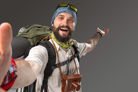 Portrait of a male smiling fully equipped tourist with backpack and the camera on gray background. tourist opened his arms, inviting travel