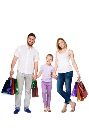 Happy family with shopping bags standing at studio, isolated on white background