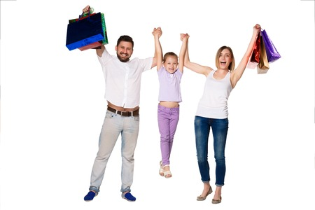 family mart: Happy family with shopping bags standing at studio, isolated on white background.  The parents raising the child in her arms