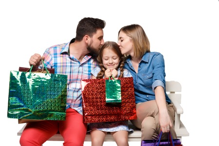 closes eyes: Happy family with shopping bags sitting at studio, isolated on white background. The parents kissing the girl, she closes her eyes in pleasure Stock Photo